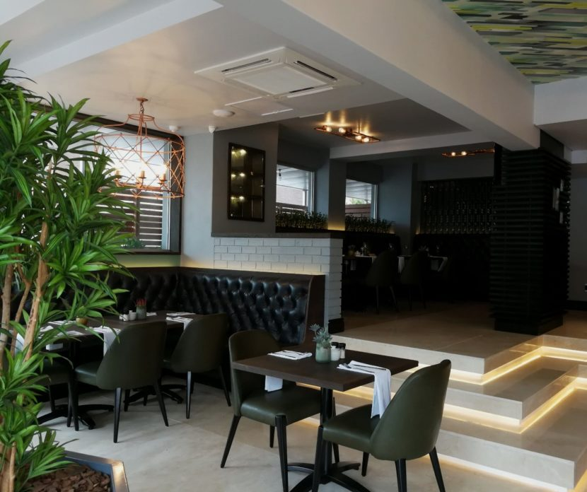 a contemporary restaurant in-set interior with dining tables, chairs & a plant